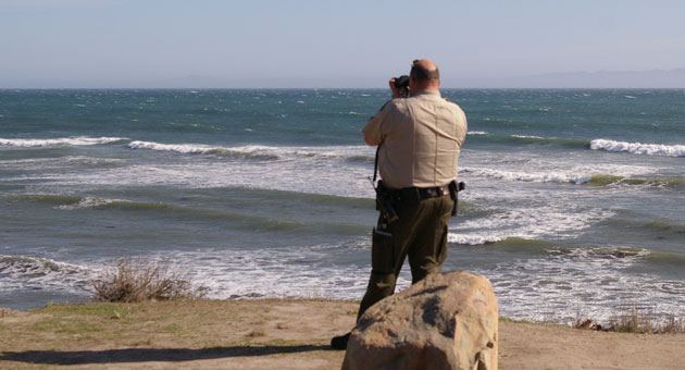 <p>A Santa Barbara County sheriff&#8217;s deputy keeps an eye on a pair of kayakers who had to be rescued after their craft overturned in high winds and heavy surf off of Isla Vista.</p>