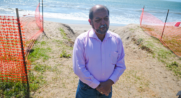 <p>Standing near orange plastic fencing that now lines Goleta Beach, City Councilman Roger Aceves talks with the media and the public on Monday about what he believes should be done to protect the park.</p>