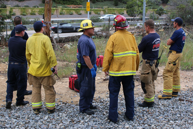 Santa Barbara police and firefighters responded Tuesday afternoon after a man was found hanged in a tree, left background, alongside Highway 101.