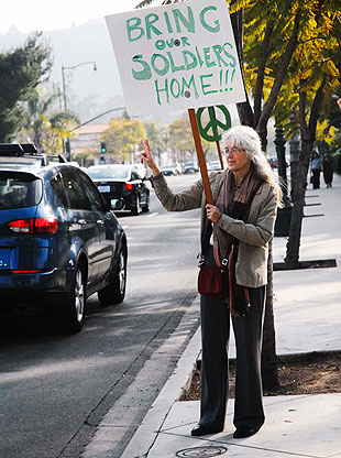 Lauren McElroy waves to passers-by as they honk in support during a peace rally Thursday.