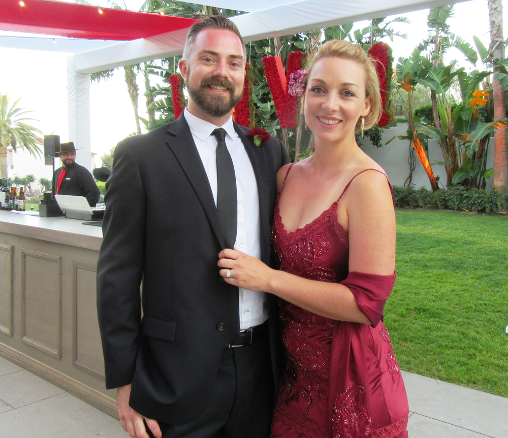 Alex and Rita Tate stand in front of the red florals created by Rita for the Laguna Blanca School gala.