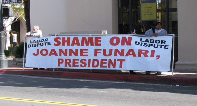 <p>Banner holders hired by the local chapter of the United United Brotherhood of Carpenters &amp; Joiners of America stand outside Business First Bank on State Street, of which Joanne Funari is president. She also volunteers with Goleta Valley Cottage Hospital&#8217;s fundraising foundation. The union has been protesting Cottage Health System&#8217;s use of a subcontractor on its project that they allege &#8220;does not meet area labor standards.&#8221;</p>