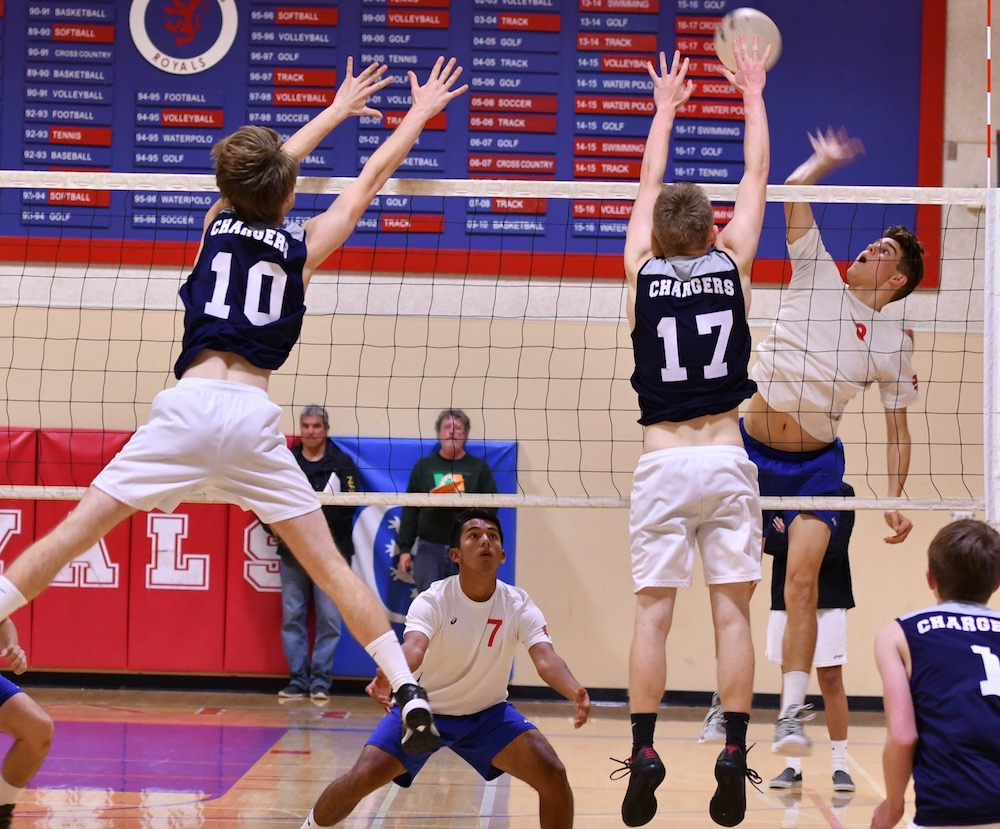 Parker Crossland (17) of Dos Pueblos blocks San Marcos outside hitter Ryder Rivadeneyra as Jimmy Kraemer (10) of the Chargers stretches to assist.