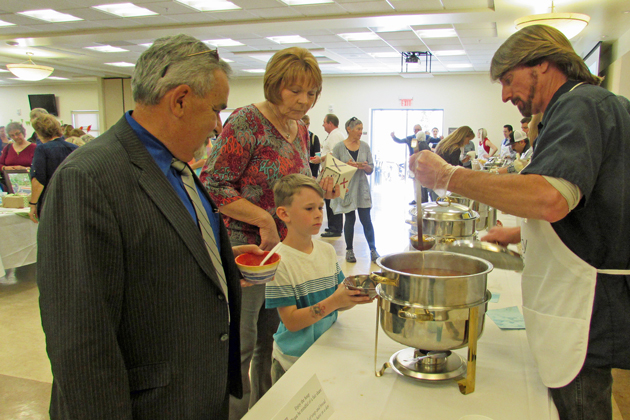Judge Rogelio Flores, left, watches as David Toy serves soup to Rhyse Schaffer, 6, while the boy's mother watches Wednesday afternoon during Empty Bowls of Lompoc.