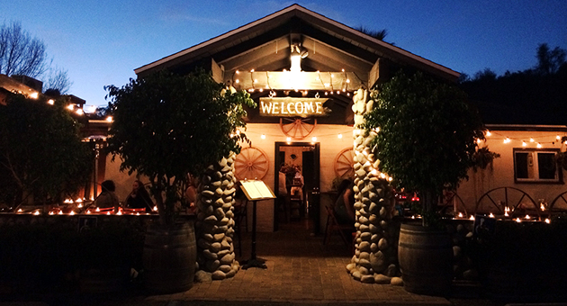 The Bourbon Room's restaurant front features a nameless welcome sign against a peaceful Santa Barbara skyline.