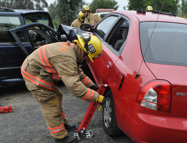 A firefighter practices accident stabilization and vehicle extrication training.