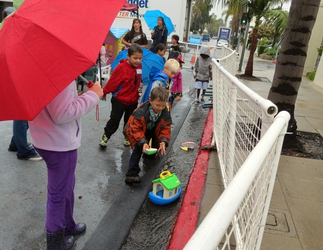 The Kids' Zone, which closed down Santa Barbara Street between Anapamu and Figueroa streets during the adult Easter service, crafted impromptu boat races using the rain water. (Gina Potthoff / Noozhawk photo)