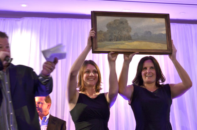 Marymount teachers Vonnie Orth and Alexa Ratcliffe display a painting by alumna and artist Meredith Brooks Abbott, class of 1956, during the gala's live auction.