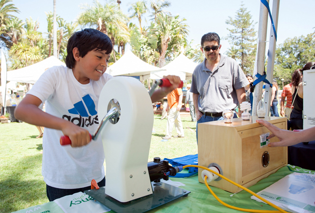 <p>A visitor to the SCEEP booth at last year&#8217;s Earth Day Festival uses a special hand-crank device to see how much energy it takes to power incandescent light bulbs versus energy-saving CFLs and LEDs.</p>