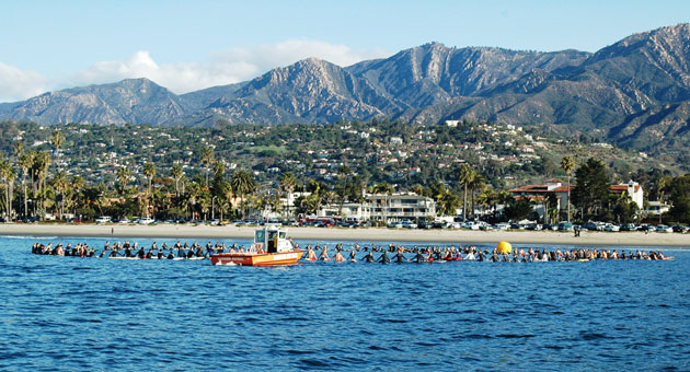 An armada of kayaks and surfboards floats off Santa Barbara's East Beach on April 5 in honor of the late Nick Johnson. (Ryan Kelly photo)