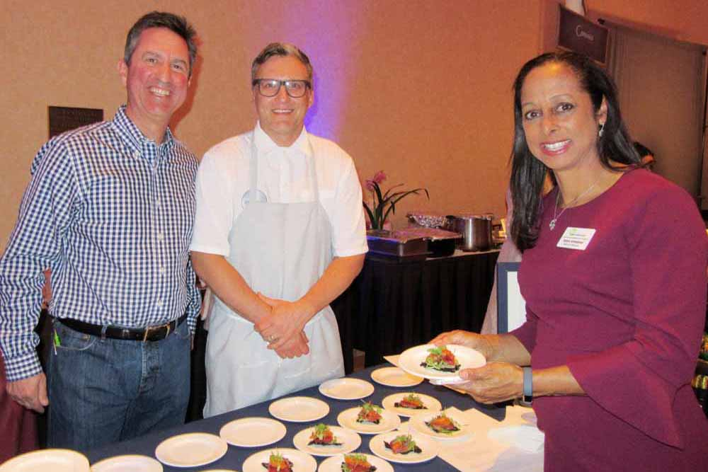 Convivo Restaurant partner Michael Mindel, left, and Chef Peter McNee serve a tasting to Katya Armistead, board co-chair for the Family Service Agency, at the 2017 Cooking Up Dreams fundraiser. McNee received the Judge's Choice Award.