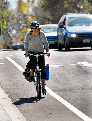 A cyclist pedals through traffic at Mission Street on a new bike lane that was installed in the area at the Highway 101 undercrossing.