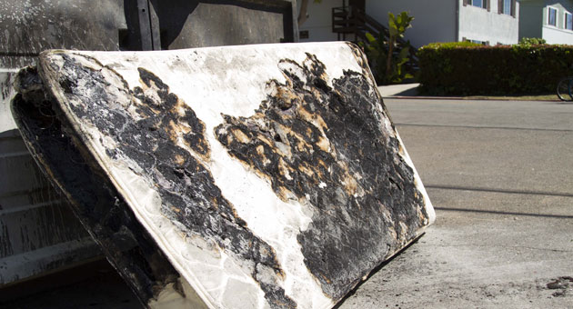 A charred mattress lies outside an Isla Vista apartment Sunday, a day after the Deltopia street party turned violent. (Justin Covington / Noozhawk photo)
