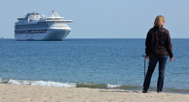 A woman strolling on Leadbetter Beach looks out at the Sapphire Princess cruise ship, which made a port call in Santa Barbara on Friday.