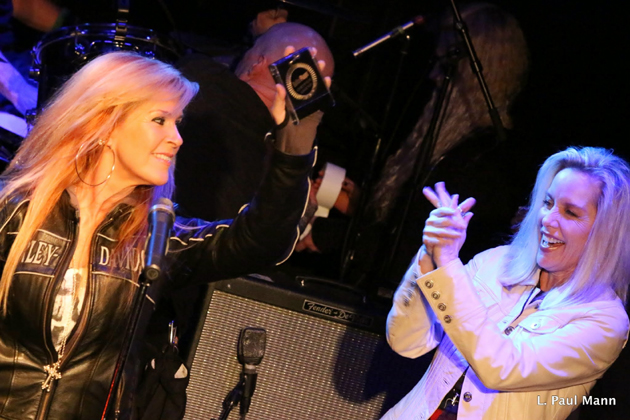 <p>Lita Ford holds up the Guitar Player Magazine&#8217;s Certified Legend award, with former Runaways bandmate Cherie Currie cheering her on. Ford and Currie also performed at the Rock Against MS event on March 26 at the Whisky a Go Go in West Hollywood. <a href=