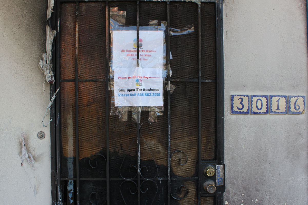 A burned door at DCM Graphics with a sign saying the business remains open despite a weekend fire.