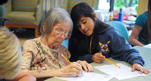 <p>Coastline Christian School fifth-grader Amaris Cabrera, 10, and Vista Del Monte resident Marilynn Seekins, 94, work together on an activity Thursday at the retirement community. The fifth-grade class travels to Vista quarterly to visit with residents and fulfill their community service projects.</p>