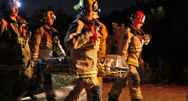 Firefighters carry a car crash victim to a waiting ambulance after a vehicle ran off Tunnel Road in Santa Barbara's Mission Canyon. (Urban Hikers photo)