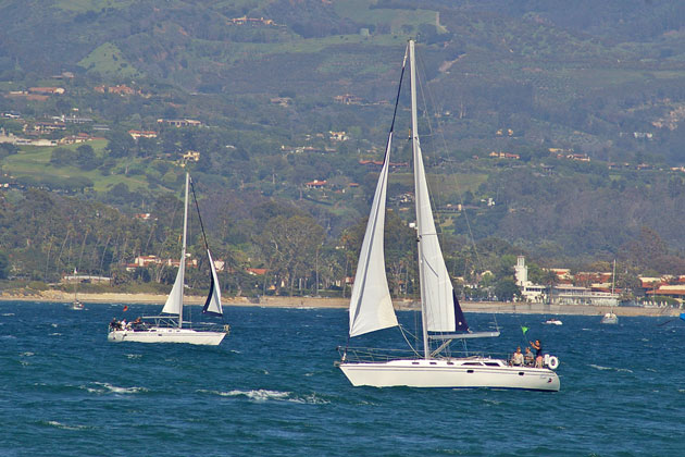 A pair of sailboats take advantage of strong winds Thursday afternoon near Stearns Wharf and the Santa Barbara Harbor.