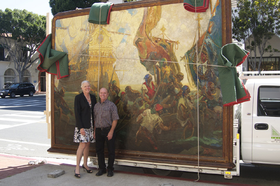 <p>Janet Garufis, president and CEO of Montecito Bank &amp; Trust, and Rodney Baker, president and director of projects for the Santa Barbara Courthouse Docent Council, stand with the &#8220;Landing of Cabrillo&#8221; painting created by Dan Sayre Groesbeck as it makes its way back to its original home at the bank&#8217;s branch on State Street in Santa Barbara.</p>