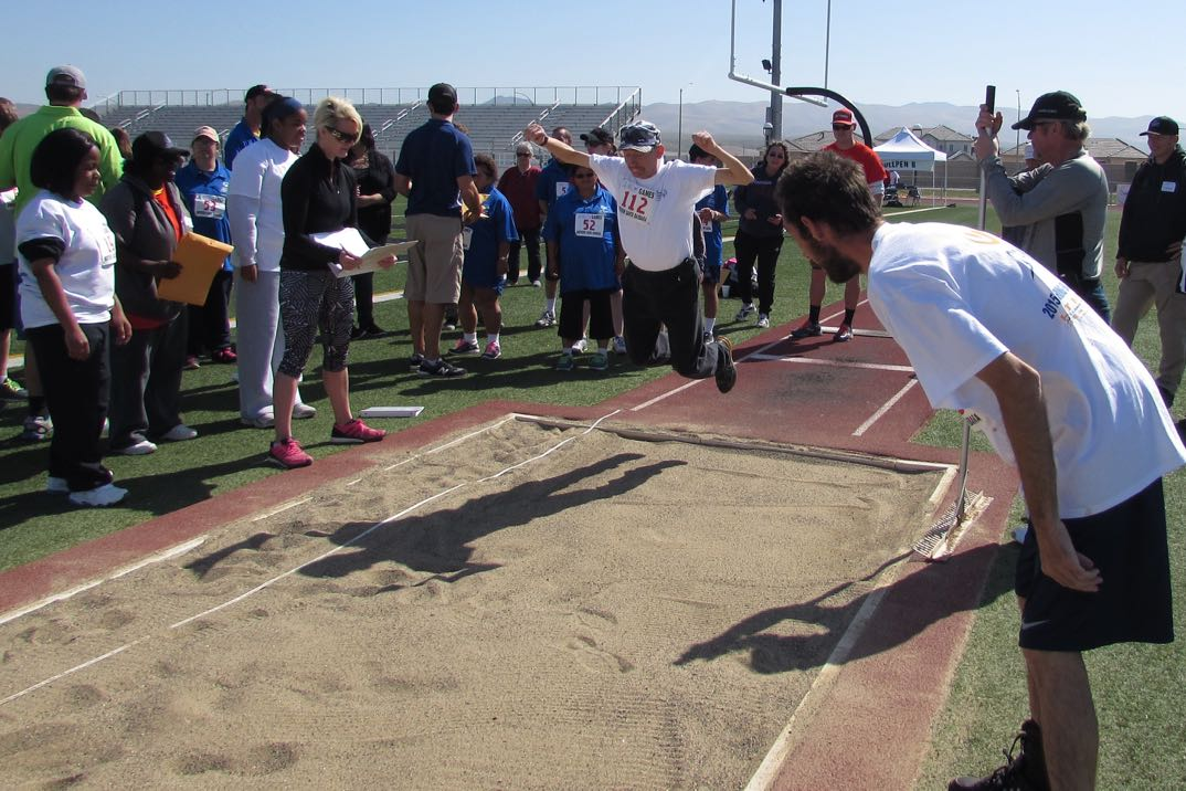 Brandon Womack competes in the standing long jump while being cheered by brother and fellow Special Olympian Joseph Womack.