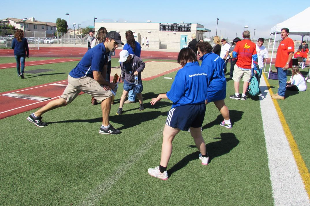 Coach Curt Direnzi encourages Santa Barbara Region Special Olympians to stretch before competing in the standing long jump.