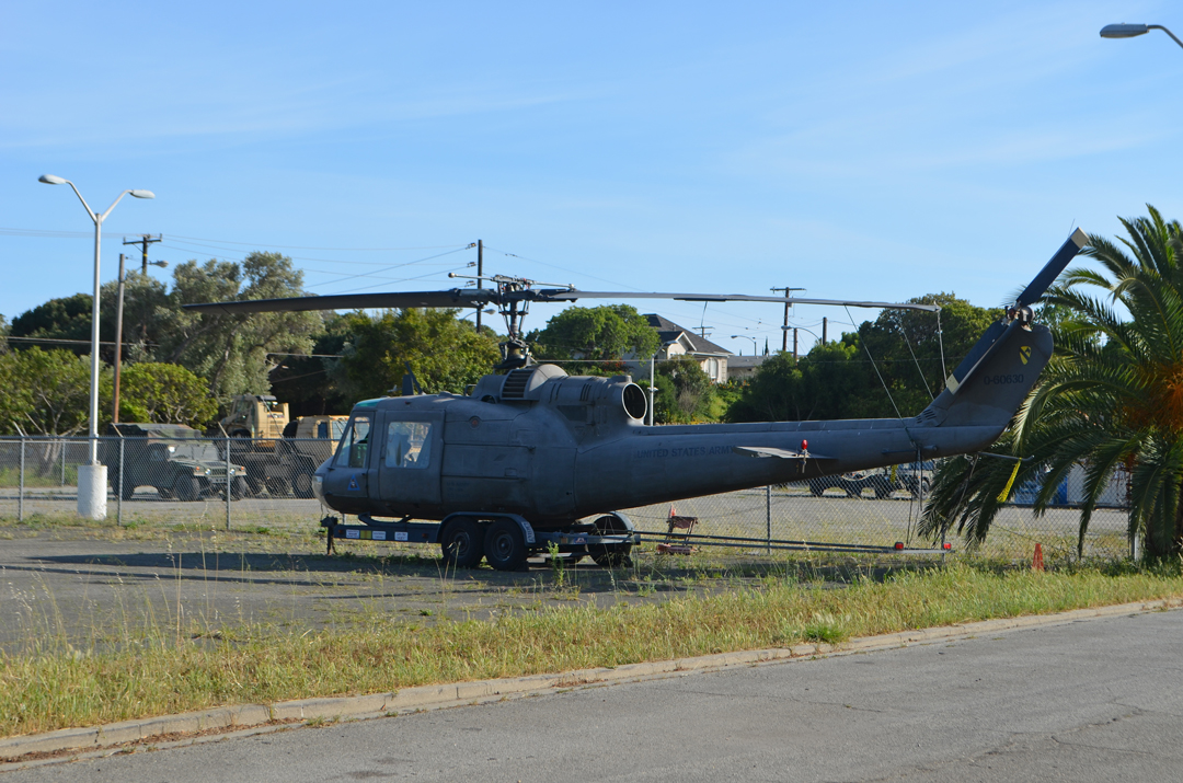 A helicopter and military vehicles are stored in the parking lot area of the Santa Barbara Armory property at 700 E. Canon Perdido St.