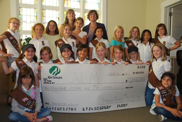 Members of Girl Scout Troop No. 50304 present CALM with a check for $500 in extra cookie revenue that will be used for a new projector at the nonprofit's offices. (CALM photo)