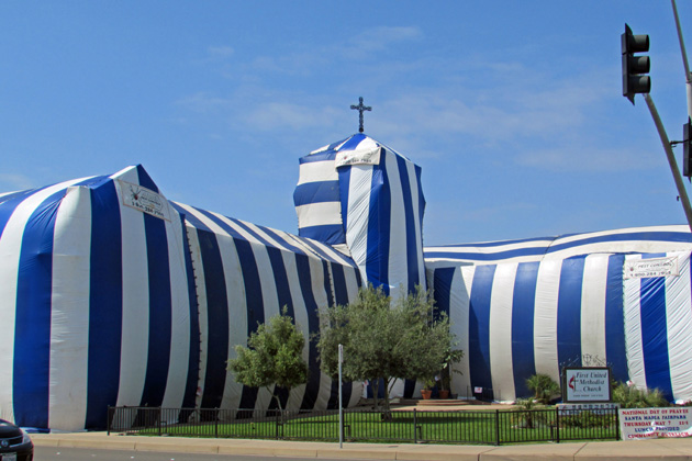 A blue-and-white striped termite fumigation tent covers all but the cross of First United Methodist Church in downtown Santa Maria on Wednesday.