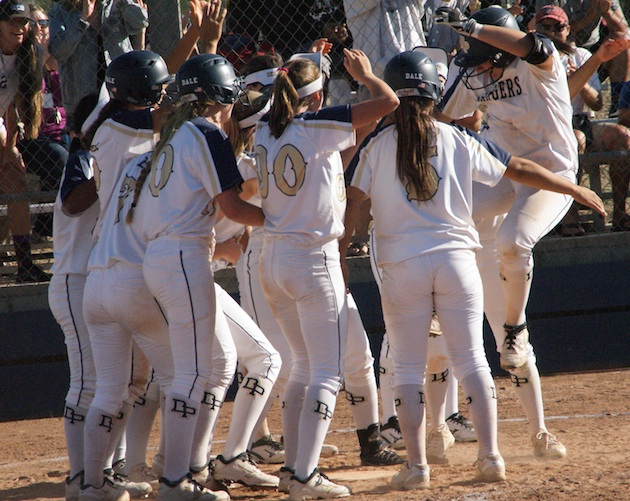Jade Sinskul leaps into home plate as her Dos Pueblos teammates celebrate her go-ahead three-run homer against Buena.