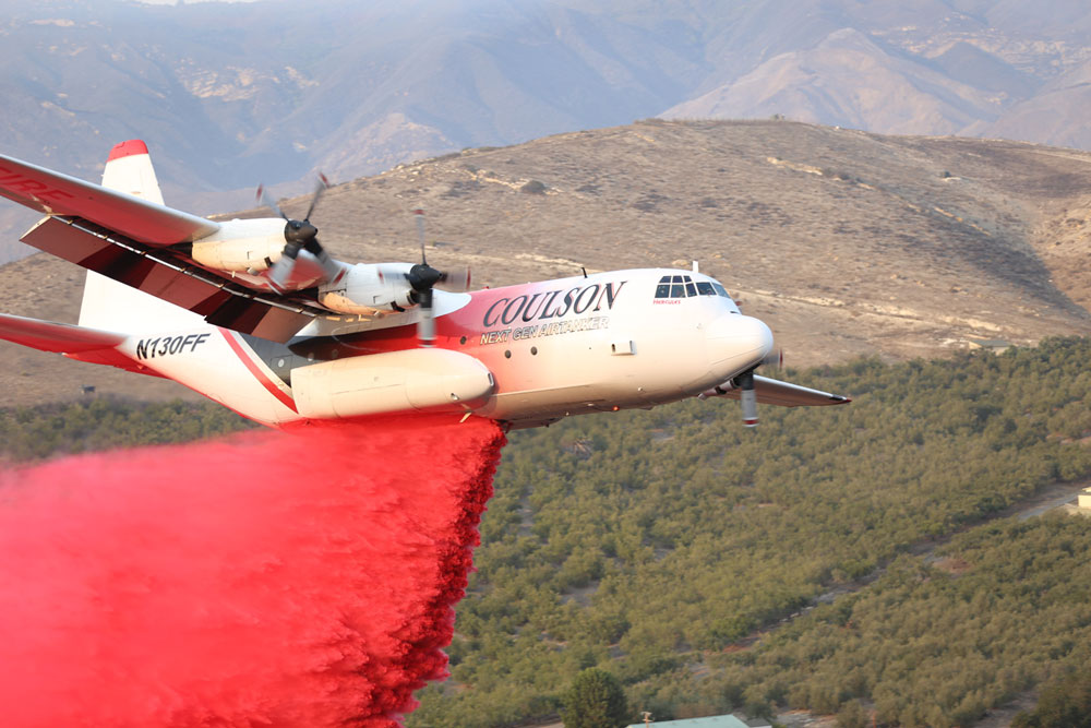 An air tanker drops a load of retardant on a vegetation fire burning Wednesday evening north of Highway 101 in the Refugio Canyon area.