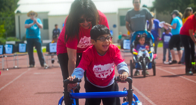 <p>Erick Rios, 7, and aide Cheryl Giordani race toward the finish line during the Special Olympics School Games on Friday at the SBCC track.</p>
