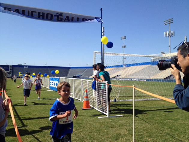Youth runners sprinted through the finish line of the Kids Dash event at UCSB's Harder Stadium.