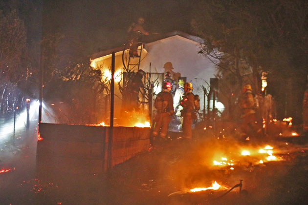 Firefighters work to extinguish flames from a wind-whipped vegetation fire that caused minor damage to a Montecito home late Sunday.