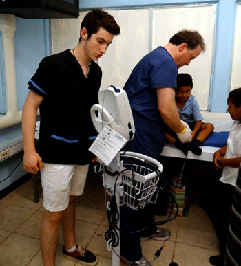Chandler Swift helps his father, Dr. James Swift, with a physical exam at a temporary clinic in Costa Rica. (Equipped 2 Heal photo)