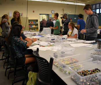 Students in the Dos Pueblos Engineering Academy work with marbles and wire to make attachments for their mobiles. (Giana Magnoli / Noozhawk photo)
