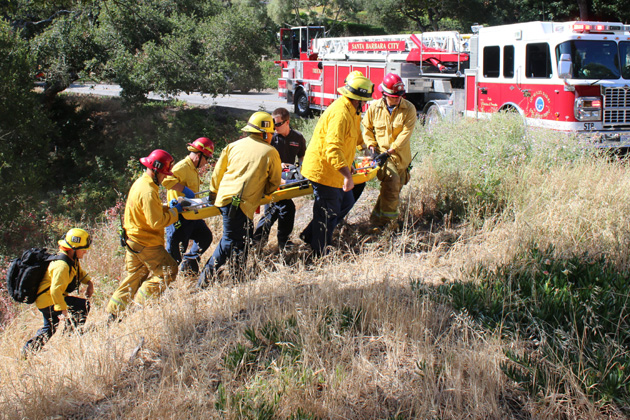A woman is carried up an embankment by Santa Barbara firefighters Monday morning after her vehicle plunged over the side of the roadway at Eucalyptus Road and Eucalyptus Circle.