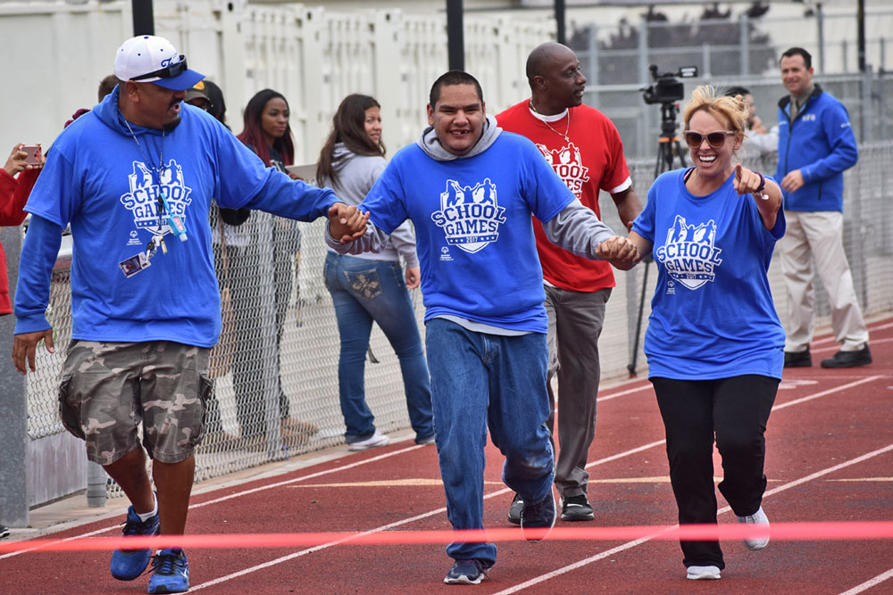 Lompoc High School staff Cesar Jimenez, left, and Sara Yeaw escort a Special Olympian down the track Wednesday during the High School Games at Pioneer Valley High School.