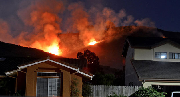 Flames from the Miguelito Canyon Fire burn behind a Lompoc neighborhood Tuesday night. As of Wednesday morning, the fire had burned 600 acres and was 50 percent contained.
