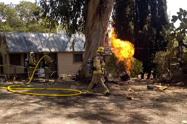 County firefighters try to keep flames away from a Solvang home during a Wednesday incident of a broken, ignited gas line in the 2900 block of Alamo Pintado Road.