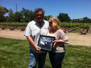 Santa Barbara Navy League President Patricia<br /> Westberg presents a signed photograph of the USS California to Eli Parker, CEO of Fess Parker Winery.
