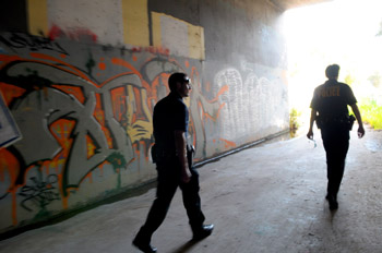Santa Barbara gang suppression officers Nathan Beltran and Sgt. James Ella walk through a drainage ditch beneath Hope Avenue.