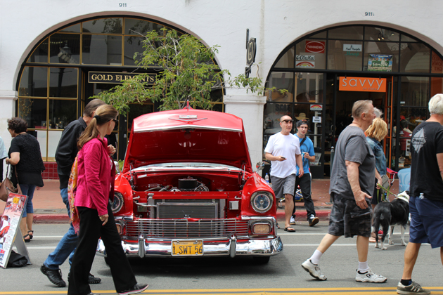 Spectators cruise by one of hundreds of vintage cars on display Sunday for the 15th annual State Street Nationals Premier Car Show in Santa Barbara.