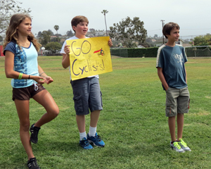 Students at Washington School in Santa Barbara hold up signs Thursday cheering on riders in the Amgen Tour of California. (Gina Potthoff / Noozhawk photo)