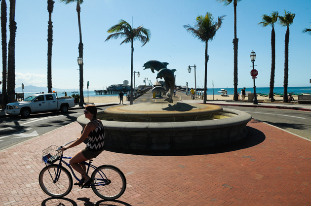 <p>A woman rides a bicycle past the dry Dolphin Fountain at the base of Stearns Wharf on Tuesday morning. The Santa Barbara City Council on Tuesday enacted stage two drought Tuesday, including prohibiting the use of large fountains.</p>