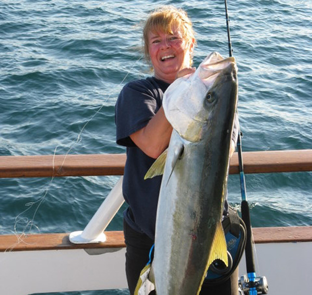 <p>Bev Seltzer celebrates a hefty yellowtail catch. These can be common during El Niño events.</p>