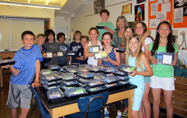 <p>Laguna Blanca School fifth-graders assemble kits containing a tile, paints, a sponge, a paintbrush and instructions for making personalized tiles to adorn a wall at the DAWG facility.</p>