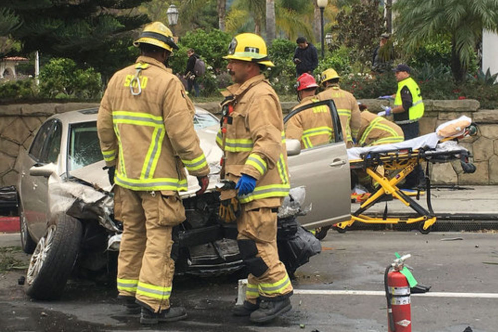 2 firefighters inspect wreckage of car