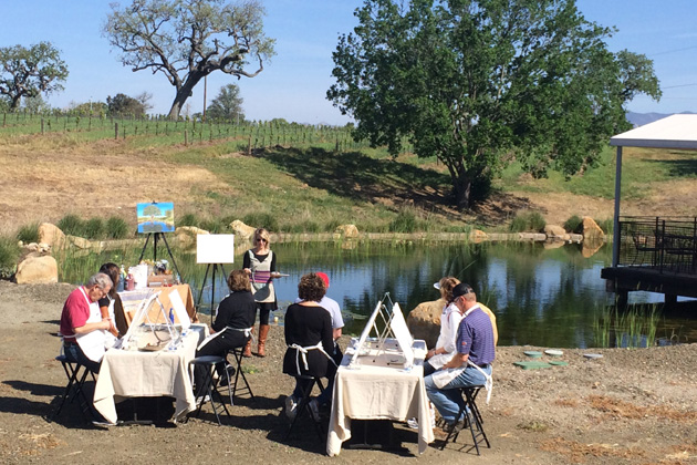 "Artist Christi Schaeffer, background in sunglasses, directs a small group ready to participate in ""Painting in the Vineyard"" at Beckmen Vineyards in Los Olivos."