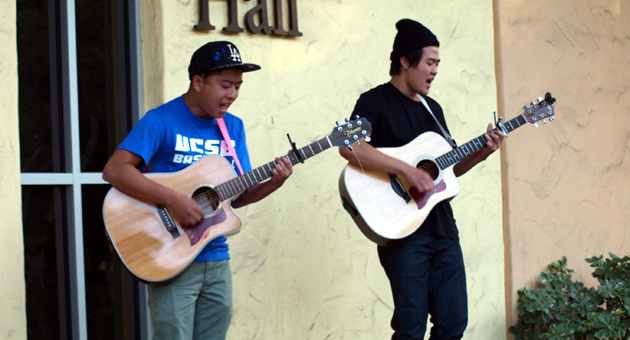 <p>Friends Tony Hui, left, and John Han lead attendees in song during a prayer and worship service in Isla Vista on Tuesday night, held to inspire comfort and healing in the wake of last week&#8217;s deadly rampage that left seven people dead.</p>